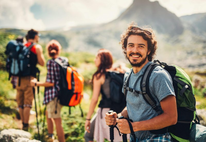 Portrait of a beautiful male hiker standing behind his friends.